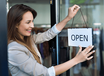 Woman small business owner puts an open sign on the door of storefront